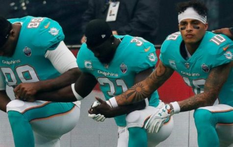 Players from the Miami Dolphins kneel to make a  statement about equal treatment.