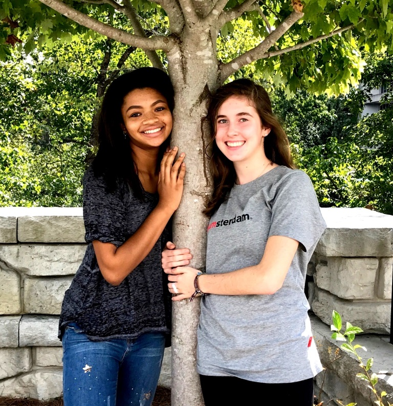 Tree Huggers: Junior Soleil Golden and sophomore Caitlin Hohenstein plant the seed of promoting the environment by helping to keep the school clean and green.