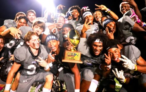 Hoco Heaven: Holding aloft the WSB Game of the Week trophy, Warrior players celebrate their 42-28 homecoming game victory over Northview. Cady Studios