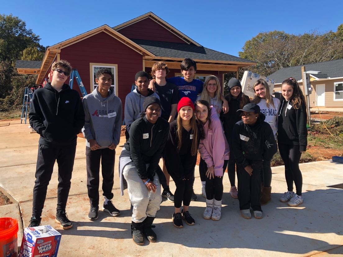 Caring Students: Members of Habitat for Humanity smile as they help the community
