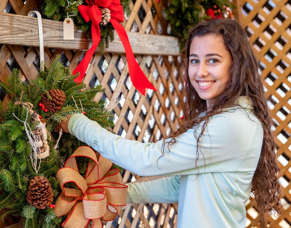 Happy Holidays: Senior Anastasia Livaditis rings in the season hanging up wreaths at Big John's Christmas Trees