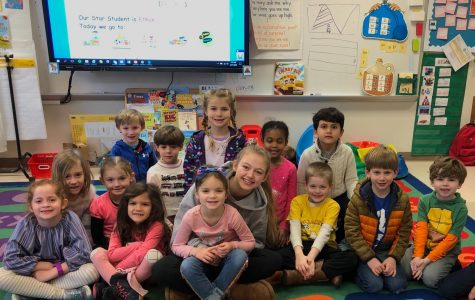 Radiant Readers: Junior Lucy-Grey Shields smiles with Jackson Elementary students