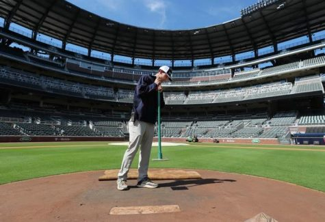 Bases Empty: An Atlanta Braves groundskeeper is the only movement in an otherwise empty Truist Park. The Coronavirus pandemic has meant a cruel springtime of no sports for sports fanatics.