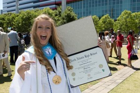 Class valedictorian Kendall De Laria celebrates with her new parchment from her alma mater, North Atlanta.