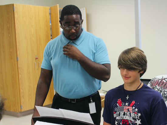 Piano teacher, Adrian Ford, assists a student during instructional time.