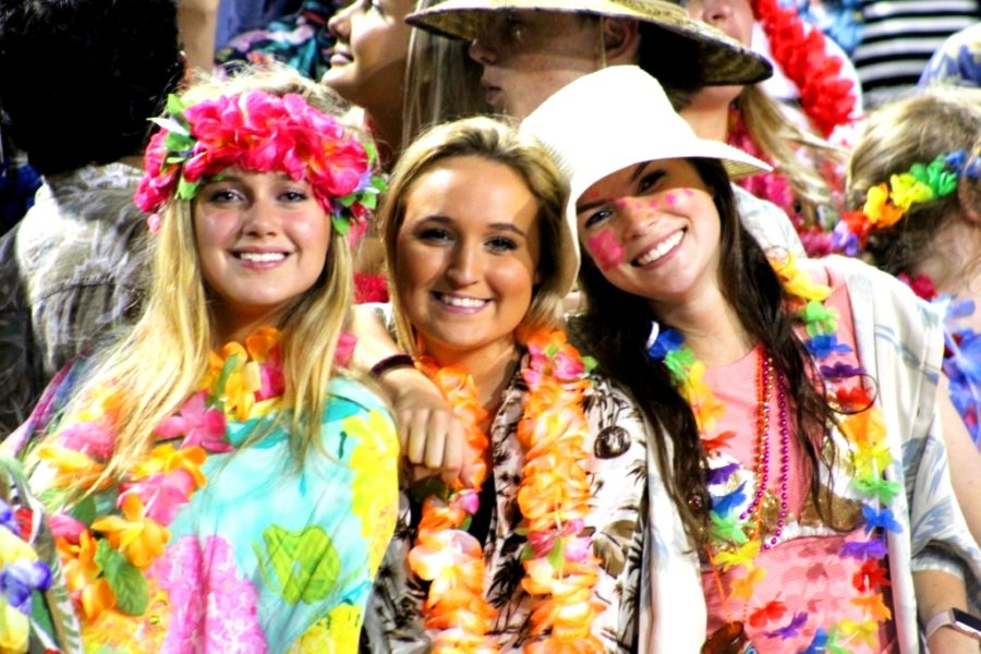 Beach Party Theme: Seniors Hanna Shaw, Annalie Chesin and Addie Derrick were part of the Warrzone crowd during the Warriors Sept. 21 victory over Cambridge. The Warrzone, organized by the North Atlanta Spirit Club, has kept spirits bright during Dub football games this fall.