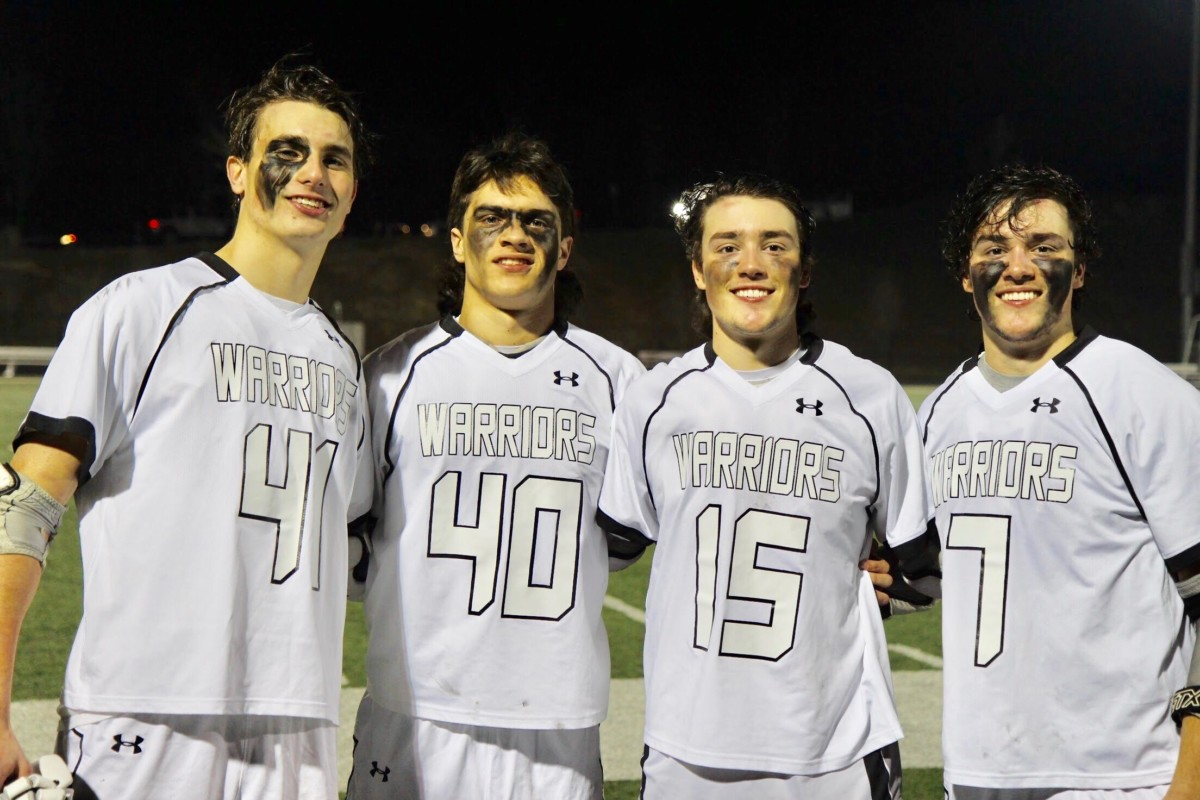 Stick Together: Junior James Brewer, junior Tommy Fialkowski, senior Mason Lassiter, and senior Devon Lassiter celebrate their most recent lacrosse game in their unique secret language.
