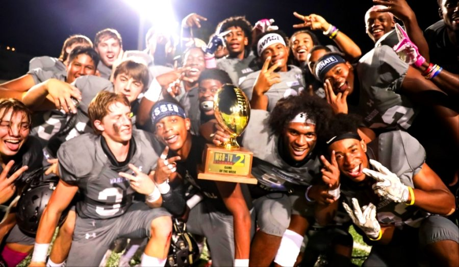 Hoco+Heaven%3A+Holding+aloft+the+WSB+Game+of+the+Week+trophy%2C+Warrior+players+celebrate+their+42-28+homecoming+game+victory+over+Northview.+Cady+Studios+%0A%0A