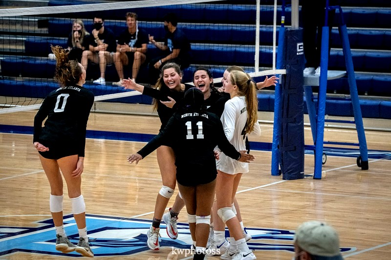 Players Maddie Bartlett, Ella McCabe, Farren Phillips, Francie Coleman, and Emilie Jacobus celebrate after a strong point winning play against the Pope Greyhounds.