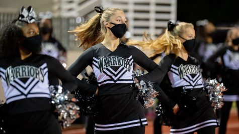 Varsity cheerleader seniors Amara Suarez, Reese Tobin and Marisa Humphreys spin toward the field as they lead things out during a cheer routine at the North Atlanta versus Tucker game on Oct. 16.